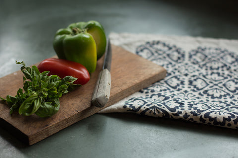 Hand-Printed Linen Tea Towel on a green slate countertop, with cutting board and knife, fresh basil and tomato