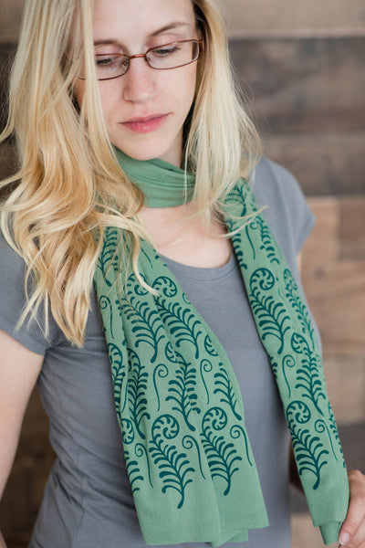 model wearing hand-printed scarf with green fiddlehead ferns pattern, handmade in Maine by Morris and Essex