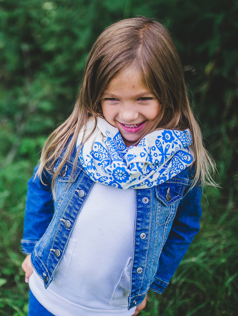 Smiling girl wearing a white hand-printed scarf with blue butterfly pattern, handmade in Maine by Morris and Essex