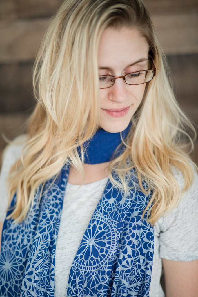 hand-printed scarf on a model with long blonde hair and glasses. Blue scarf with lacy silver pattern, handmade in Maine by Morris and Essex