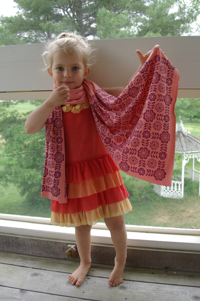 young girl wearing a handmade coral scarf, hand-printed scarf with geometric tile pattern, handmade in Maine by Morris and Essex