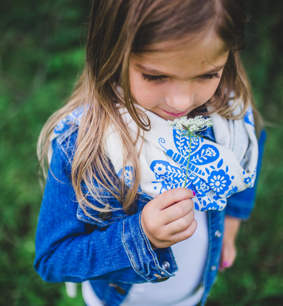 Girl wearing a white hand-printed scarf with blue butterfly pattern, handmade in Maine by Morris and Essex