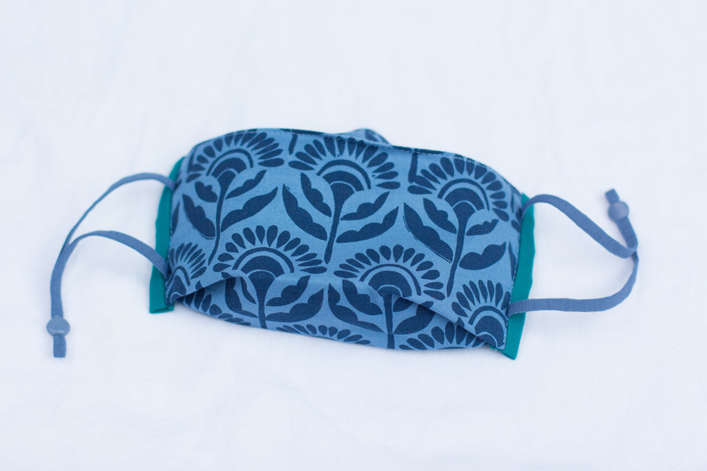 Blue face mask with hand-printed floral pattern on a white background. Handmade Face Mask with cotton and synthetic triple layer filtration. Hand-printed and handmade in Maine by Eliza Jane Curtis