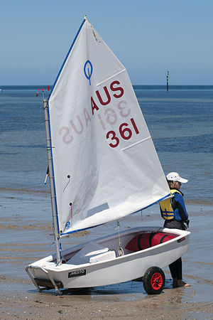 Optimist sailing dinghy with sails up on the beach