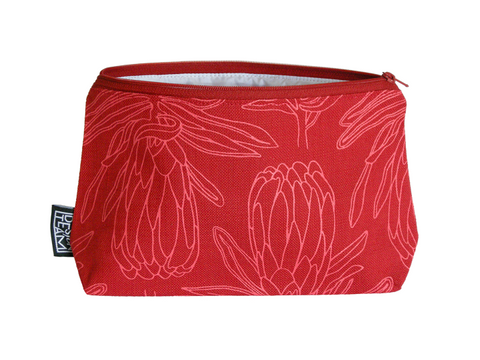 Cotton cosmetic bag with a masala coloured protea motif on a brick red background.