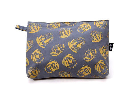 Grey bathroom bag with mustard coloured protea design and carry tag.