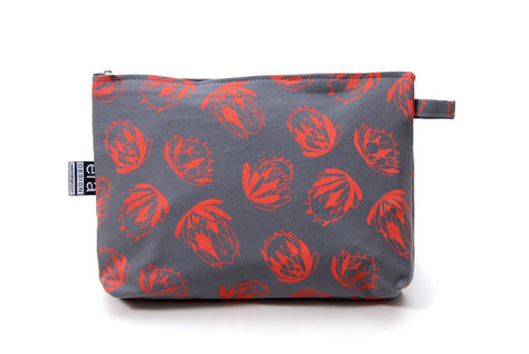 Grey bathroom bag with orange protea design and carry tag.