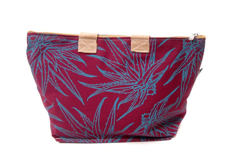 Spacious cotton vanity bag with wide base, carry handles and zipper. Turquoise Aloe Design on Maroon Background.