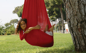 A girl is in a red sensory swing attached to a tree.