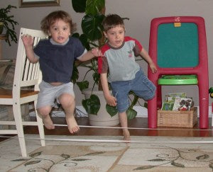 Two boys are jumping over elastic band.