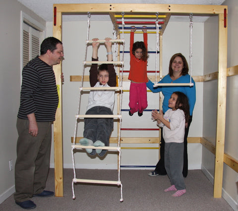 Home gym for kids installed in the basement. There are three kids playing on the jungle gym and mom and dad are supervising them.