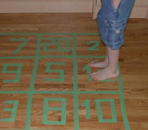 Numbered squares on the floor made of masking tape. A child is standing on one of the squares prepared to jump to the next number.