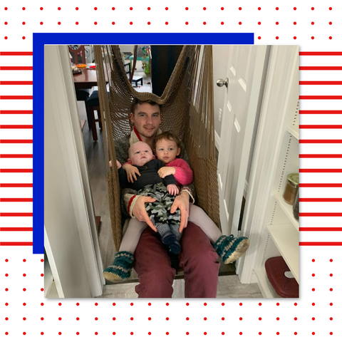 A dad is sitting in a hammock swing installed in a doorway with his two young kids.
