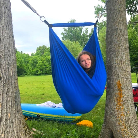 A girl is enjoying a sensory swing installed between two trees.