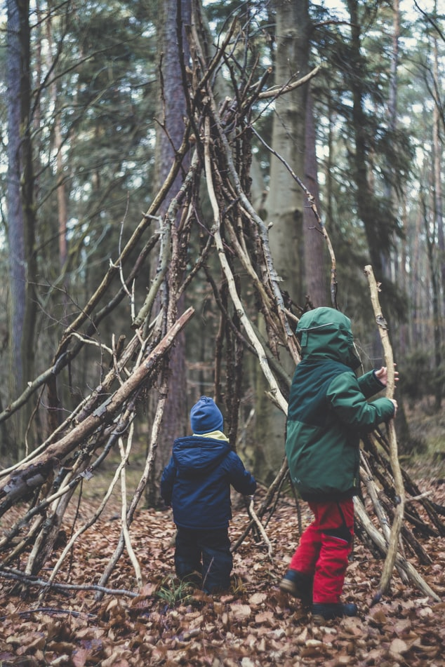 Two children are playing outside playing with sticks building a shelter.