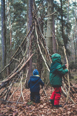 Children are playing outside, building a shelter with sticks