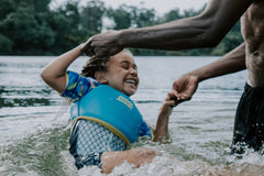 A dad is playing with a daughter in water, that looks like a lake or river. The girl is very happy, smiling