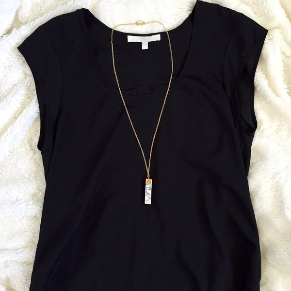 Long white rectangle necklace on black shirt