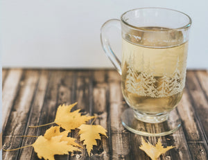 tea in etched glass mug with leaves