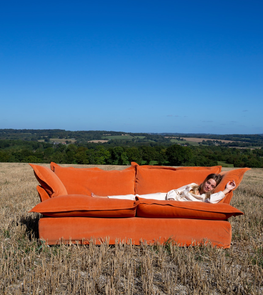 Marnie laying down on a Song Sofa covered in Burnt Orange Corduroy in a field in late summer