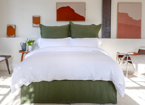 Cosy bedroom with green linen bedsheet and colourful decoration