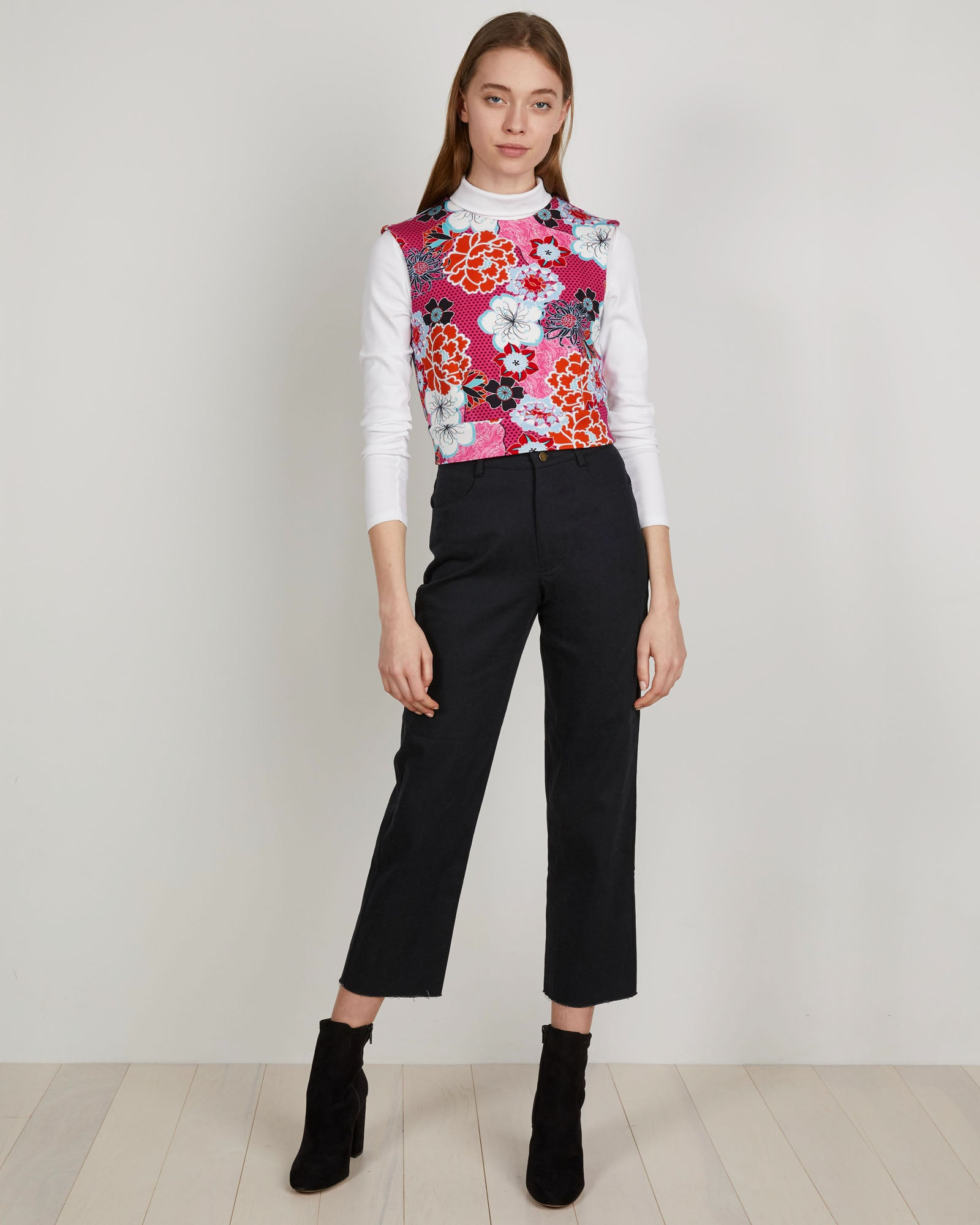 THE KIT's Leah Vest under white turtleneck in Pink Pop Floral print is a seasonless layering piece that hits at the natural waist with a fitted silhouette. Centerback zipper hardware and a spongey heavy rayon.