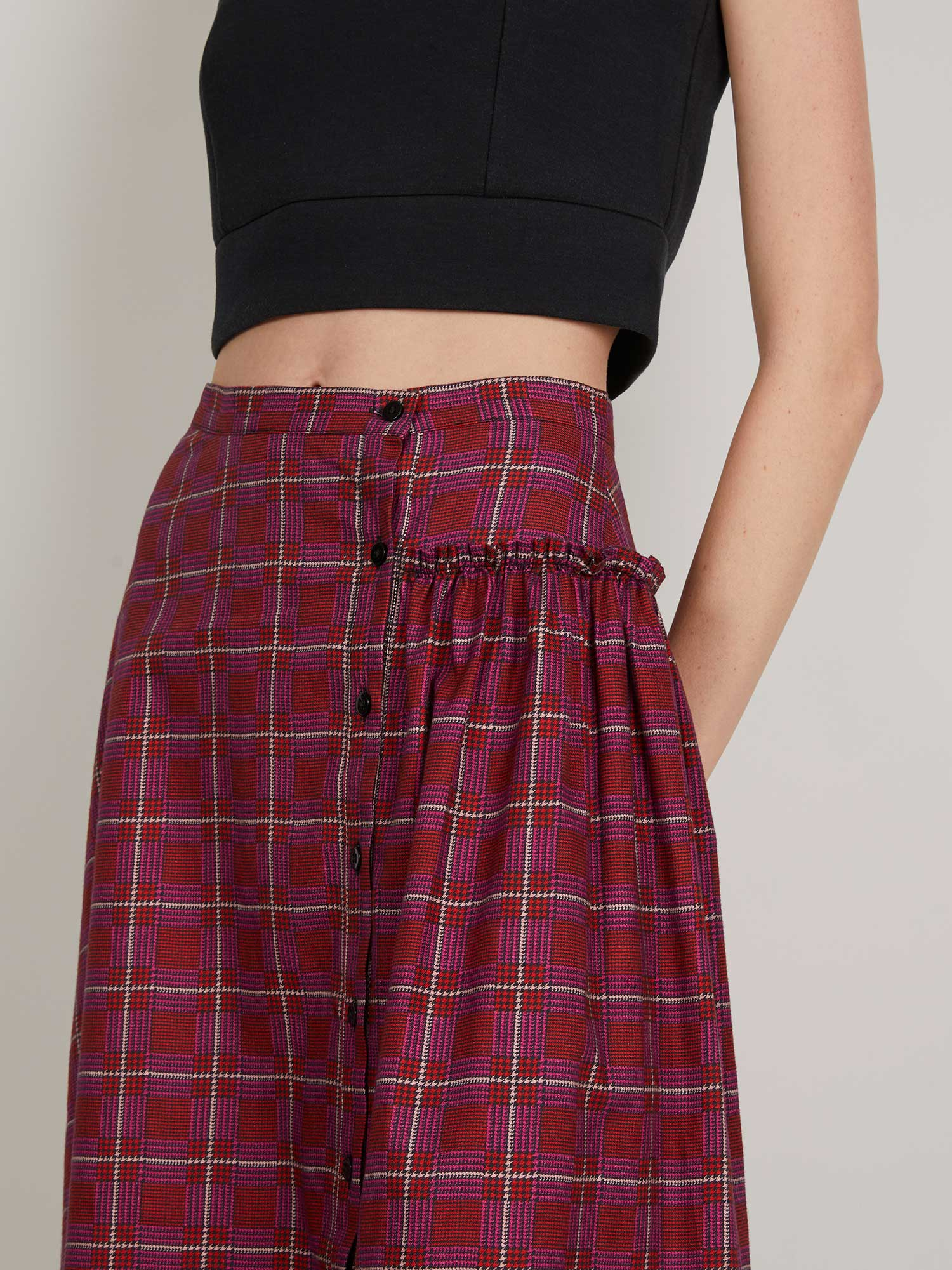 Dorothy Skirt in red plaid is an off-center, button-front full skirt with a fitted waist, asymmetrical gathering and dropped hem.