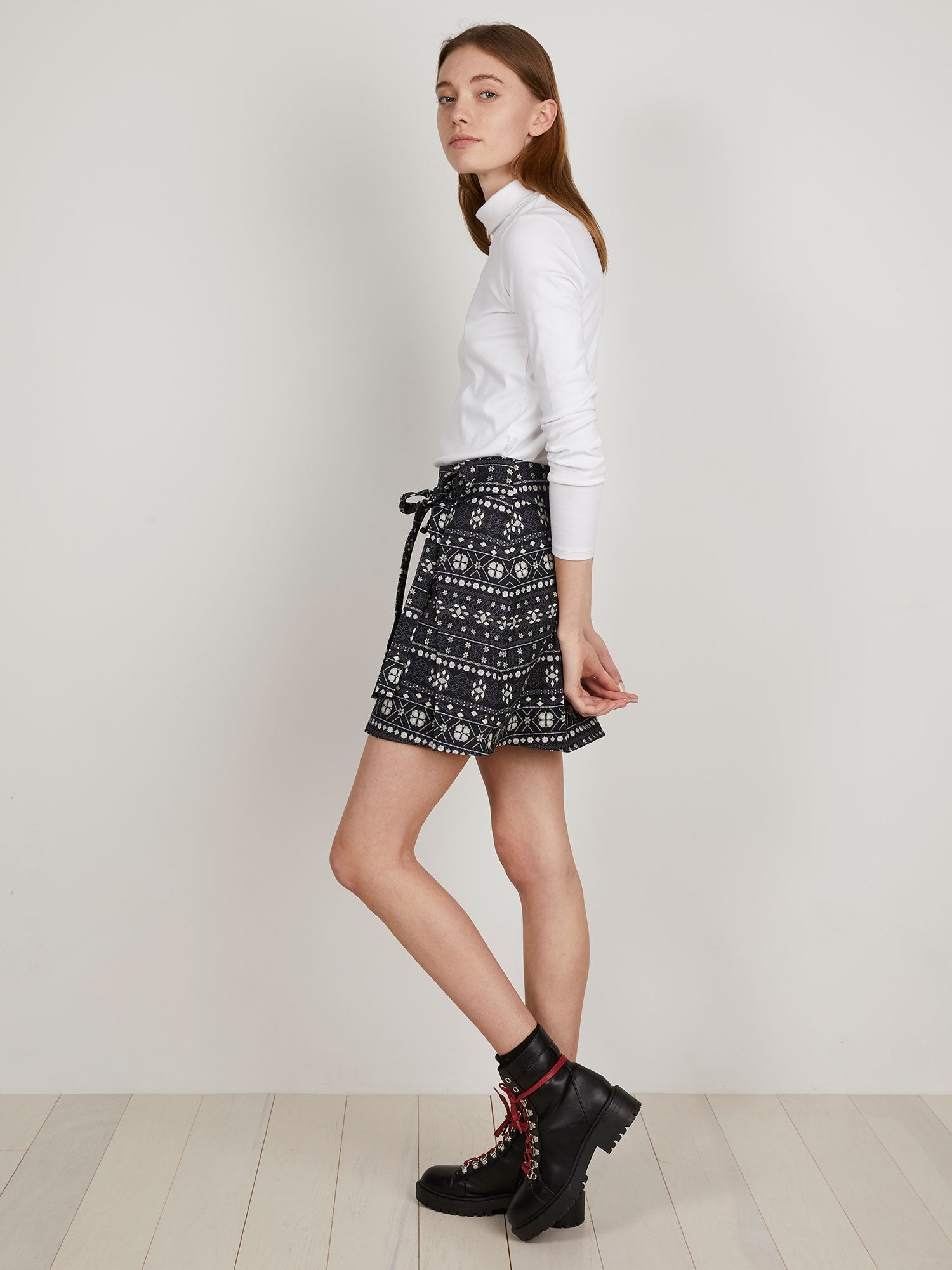 THE KIT's Wrap Kilt Skirt is a mid-thigh brushed cotton skirt side-front waist tie and cargo pocket with bold navy print black boots red laces