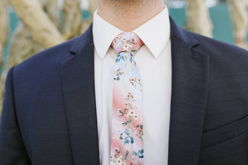 man in white suit and pink and blue flower tie