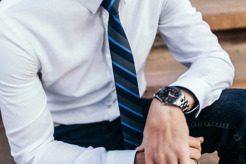 closeup of grey and navy striped tie against white shirt