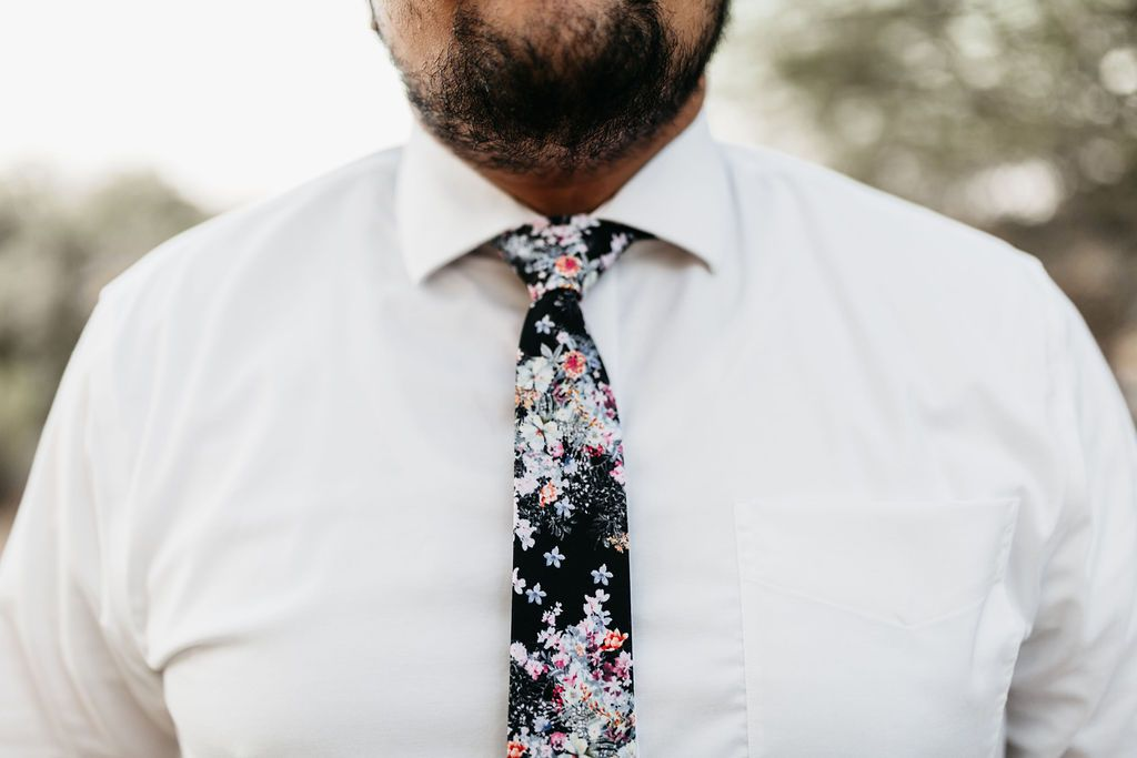 closeup of man in white shirt with black floral tie