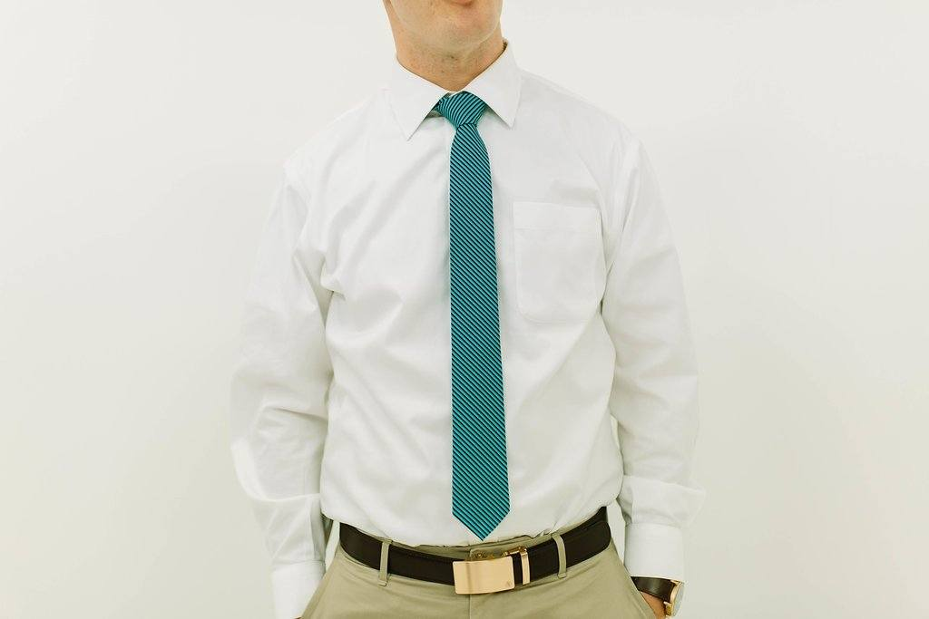 man in white shirt and green and black striped tie