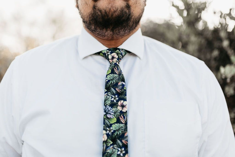 closeup of man in white shirt and green tropical floral tie
