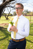 man holding flowers wearing a yellow floral tie