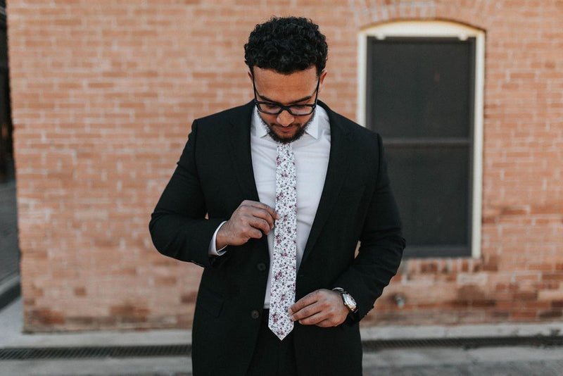 man starting at his white floral tie