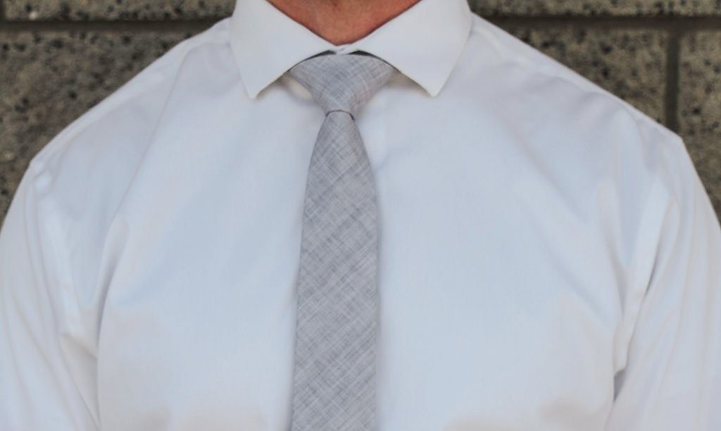 closeup of solid grey tie against white button up shirt