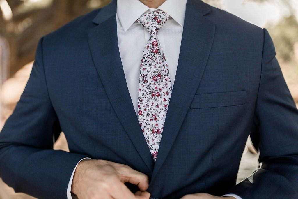 closeup of man in navy suit and red roses white floral tie