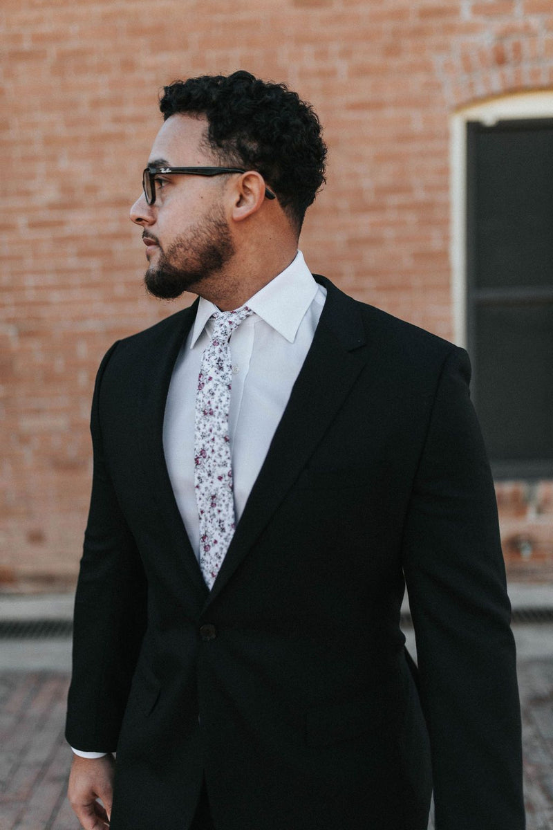 man in black suit and red roses floral tie