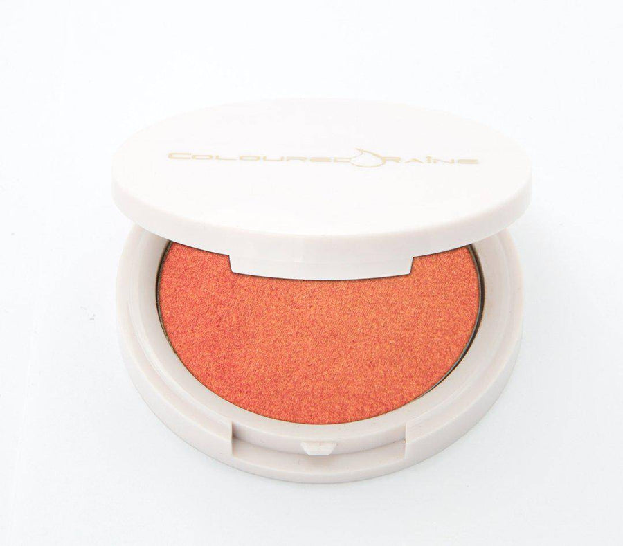 Peach highlighter with gold undertones, in a half-open container