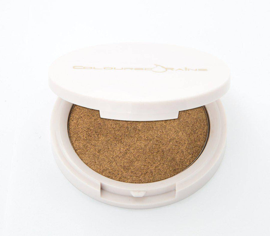 Your Treat - Golden bronze  highlighter by Coloured Raine Cosmetics. Half-open, in a white, circular, mirrored container.