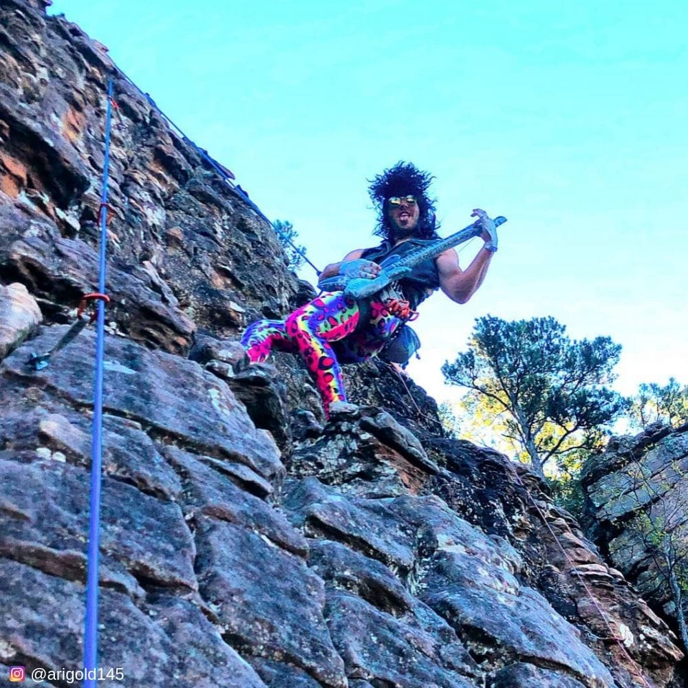 Playing guitar on a cliff in multicolor mens leggings