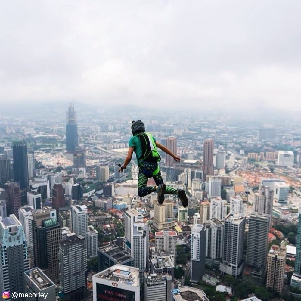 Man base jumping off cliff in male leggings