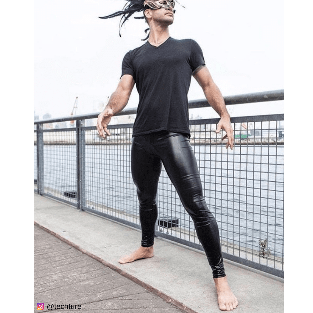 Young man in black mask and shiny male leggings by the water