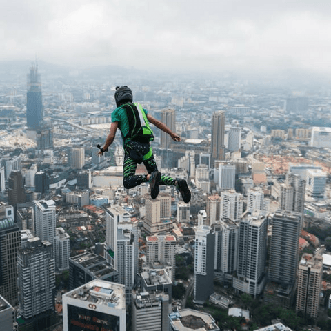 base jumper flying over city wearing black and green male leggings