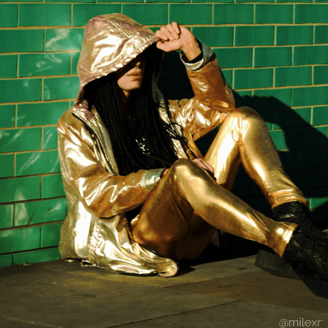 cool fashion blogger in gold men leggings and hoodie against green wall