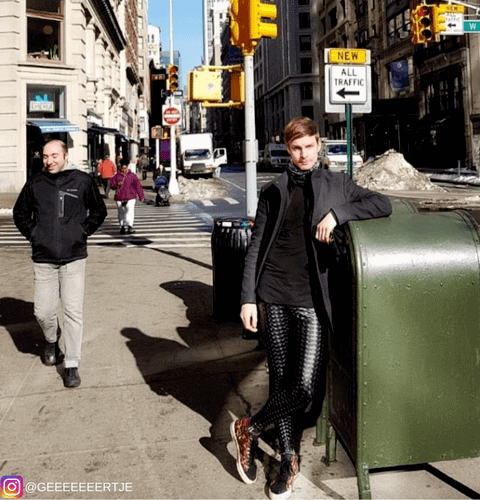 cool fashion man leaning on mailbox in black hologram male leggings