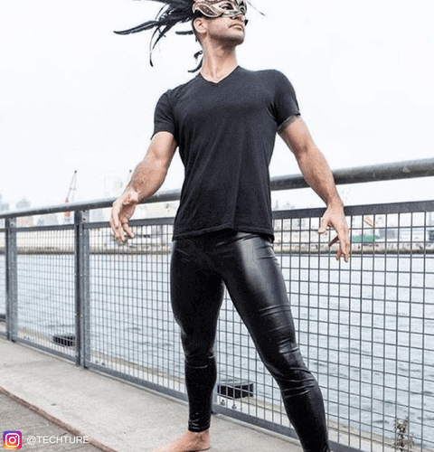 male blogger wearing carnival mask and black shiny leather leggings