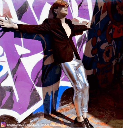 male model wearing silver leggings and black jacket leaning on graffiti wall