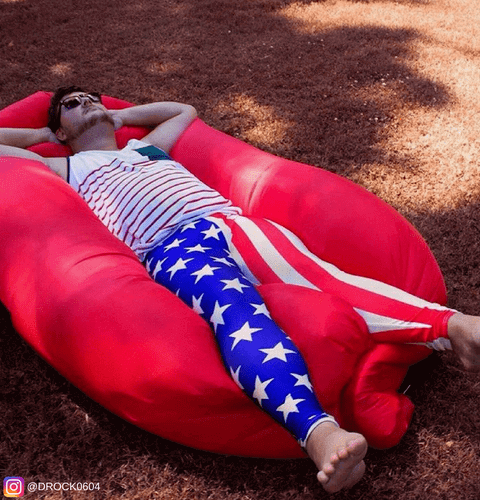 man at festival in inflatable hammock wearing usa stars and stripes leggings for men