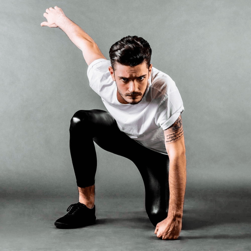 man croushing in superhero pose wearing shiny metallic black leggings
